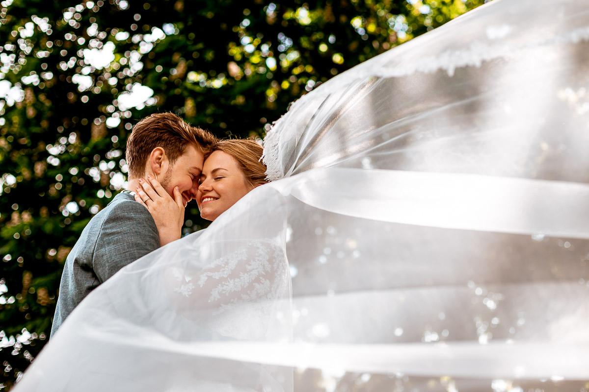Bruidspaar knuffelt terwijl de sluier in de lucht waait