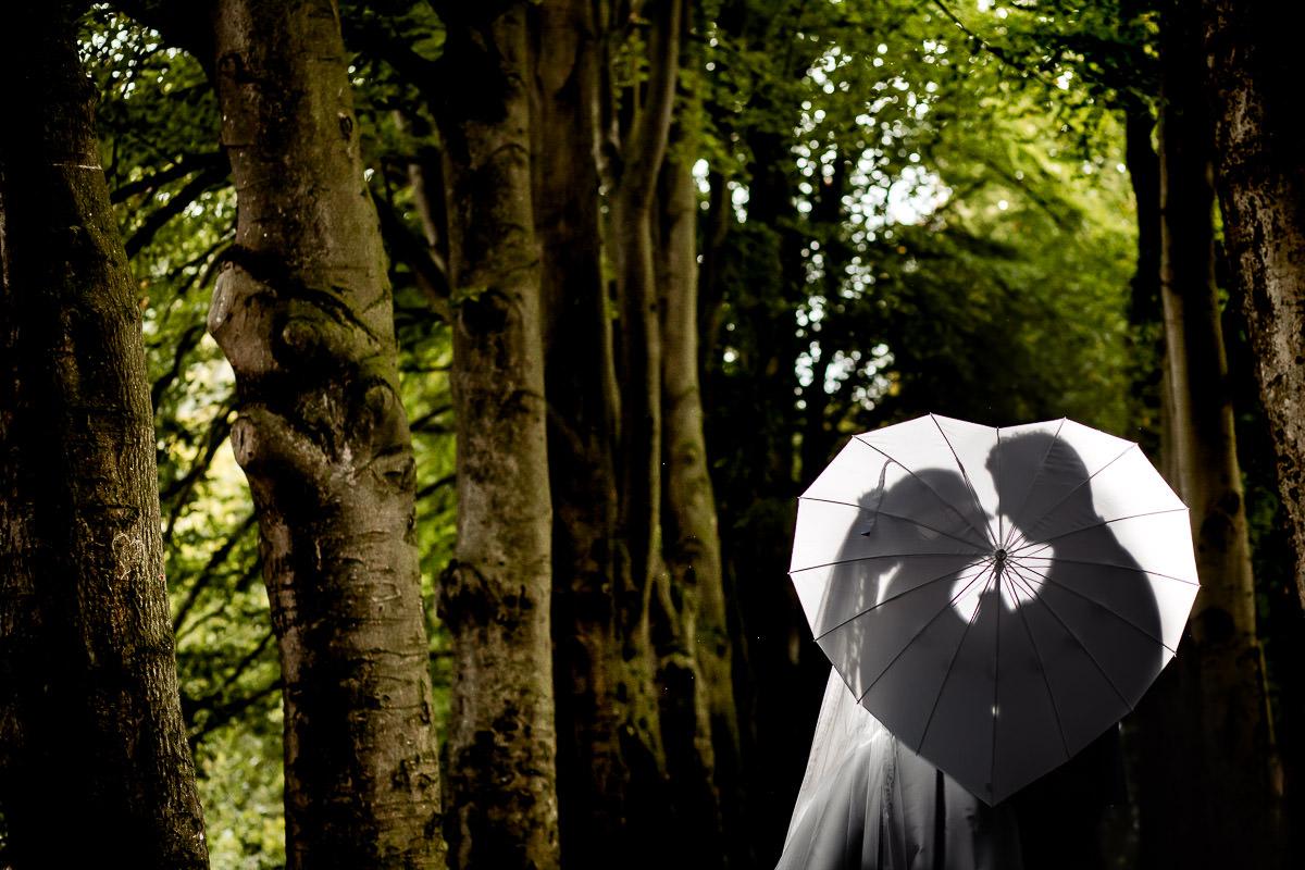 Bruidspaar staat achter een licht doorlatend paraplu