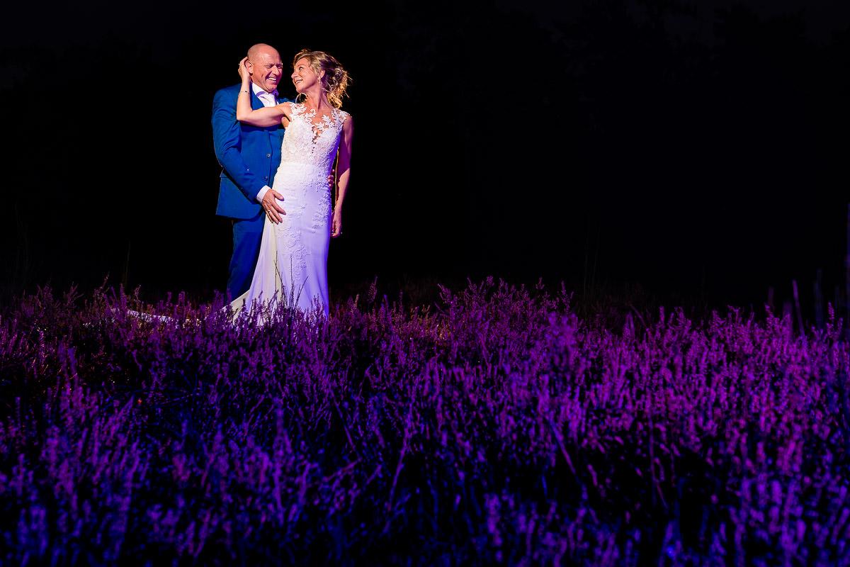 Bruidspaar staat in een heide veld