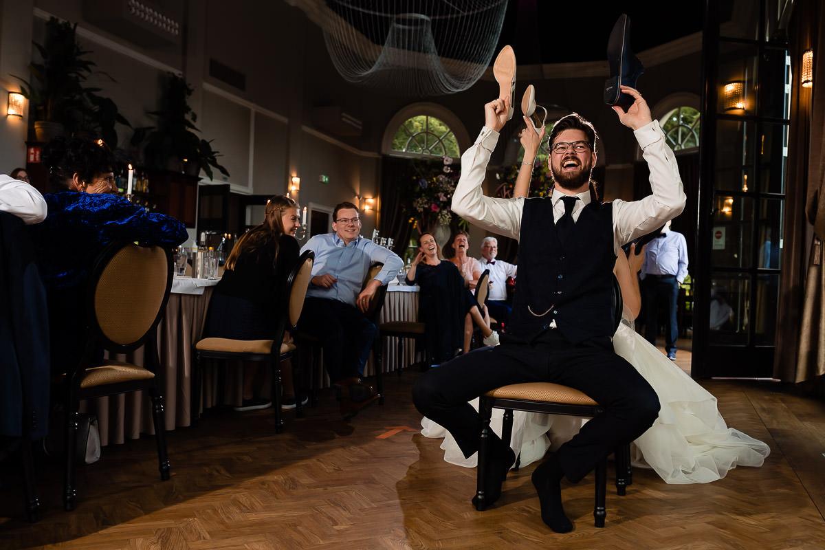 Bruidspaar houd lachend schoenen in de lucht