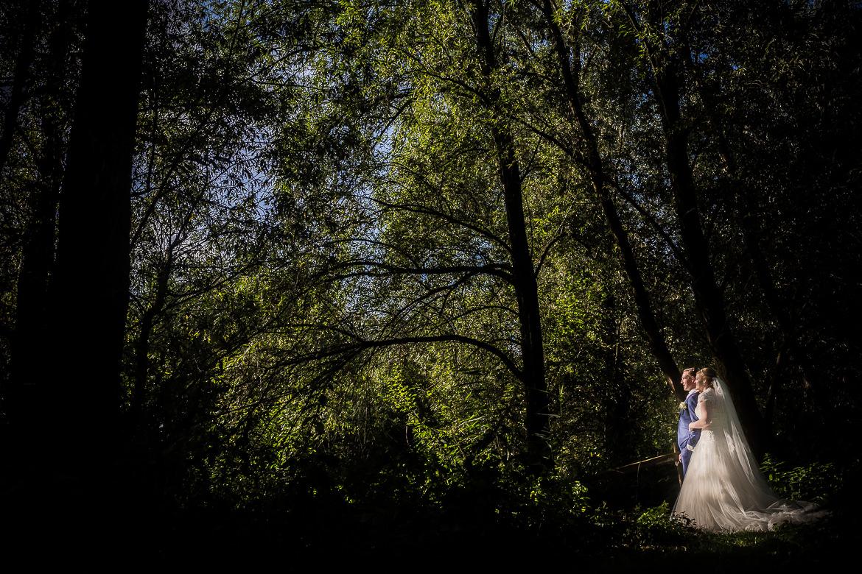 Bruidspaar poseert in een groen bos