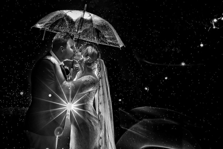 Zwart wit foto van bruidspaar onder een paraplu in de regen