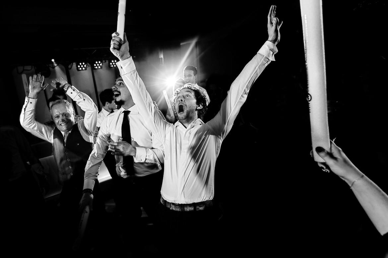 Zwart wit foto van avondgasten die los gaan op trouwfeest