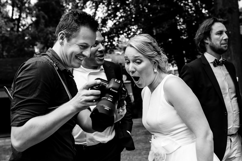 Zwart wit foto van bruidsfotograaf die foto laat zien op de camera aan de bruid