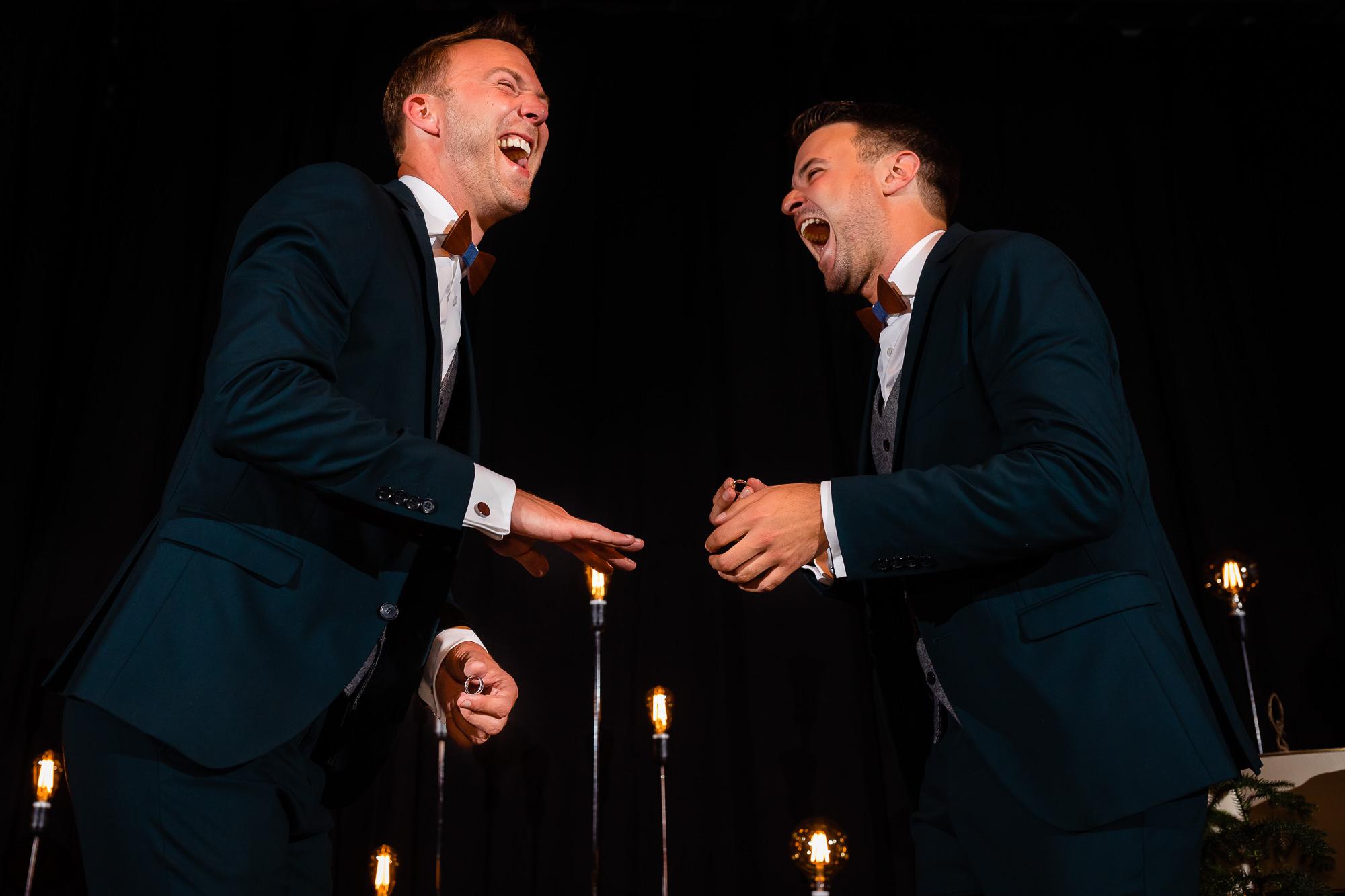 Bruidegoms aan het lachen tijdens het aandoen van de ringen