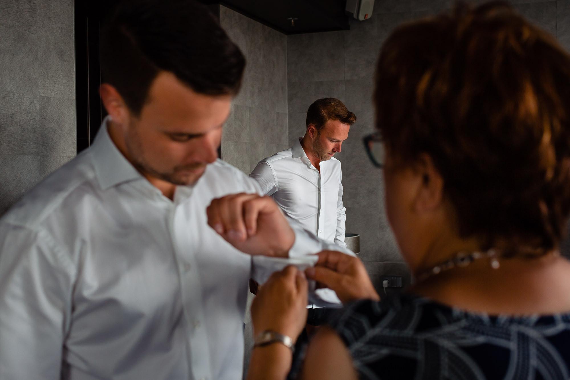 Moeder van de bruidegom helpt met het aankleden van haar zoon