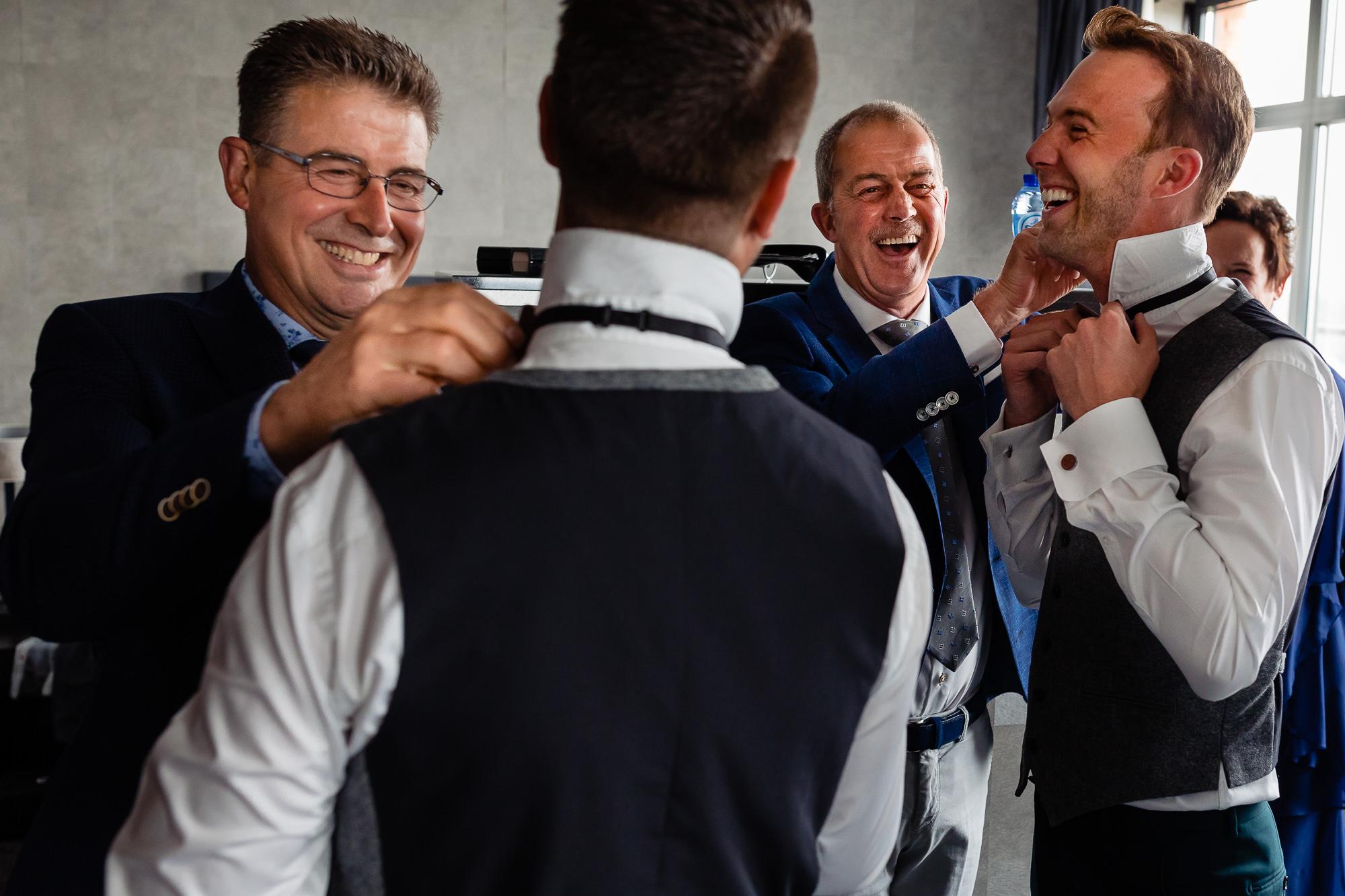 Vaders van de bruidegoms helpen beiden mee met het aankleden van hun zoons