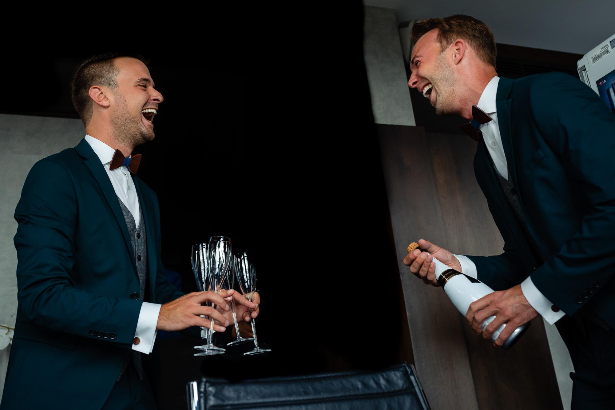 Bruidegoms trekken een fles champagne open