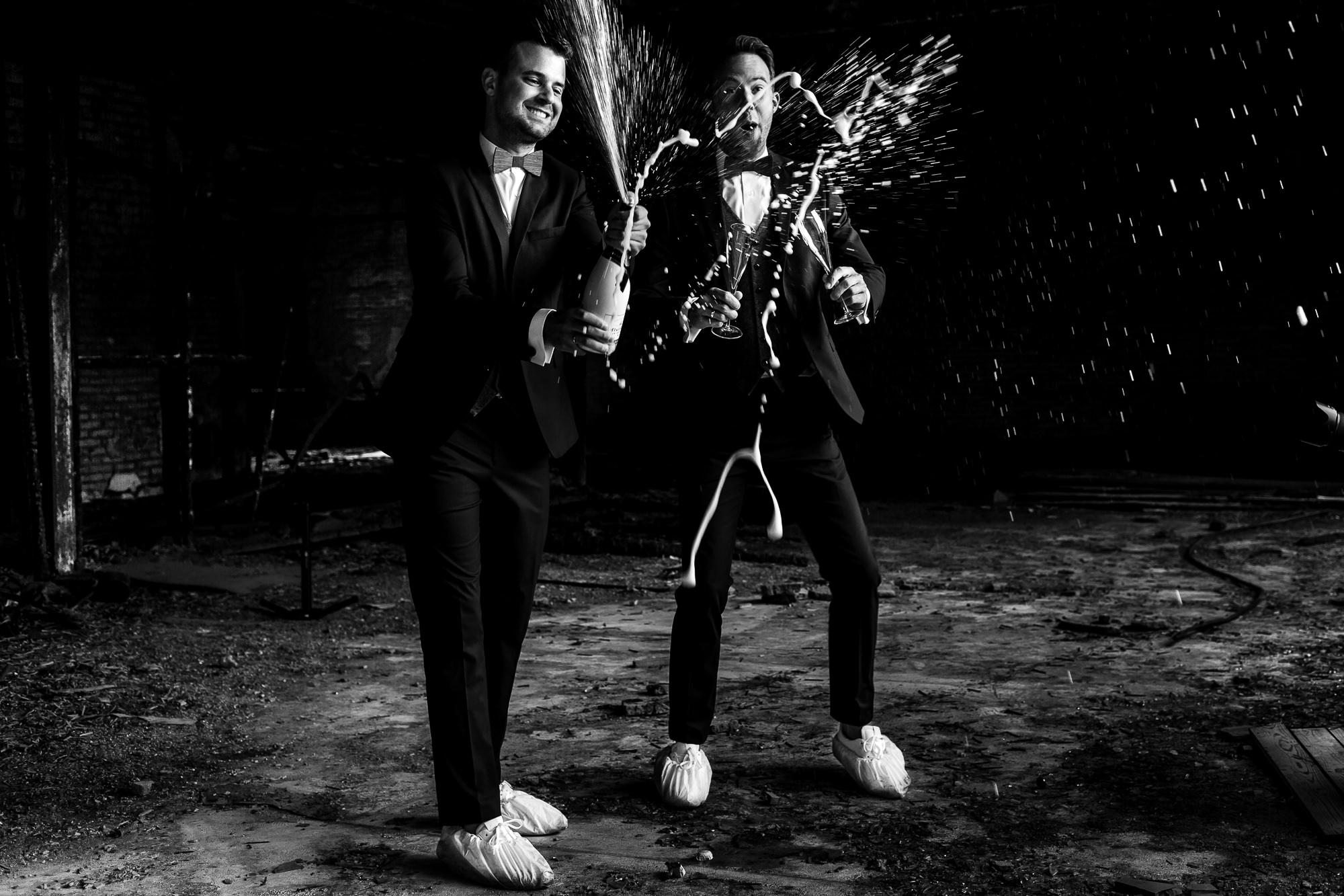 Zwart wit foto van bruidegoms die spuiten een fles champagne leeg