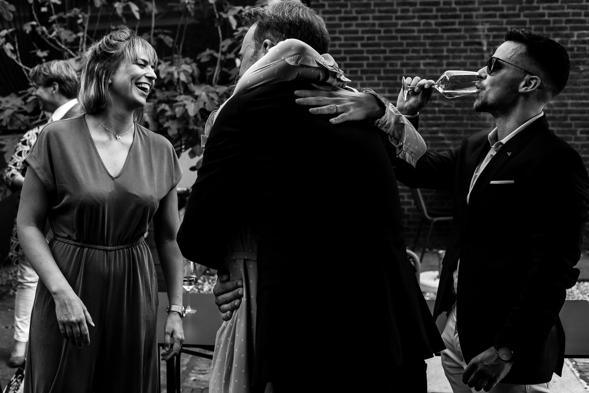 Zwart wit foto van mensen die elkaar omhelzen en man die champagne drinkt
