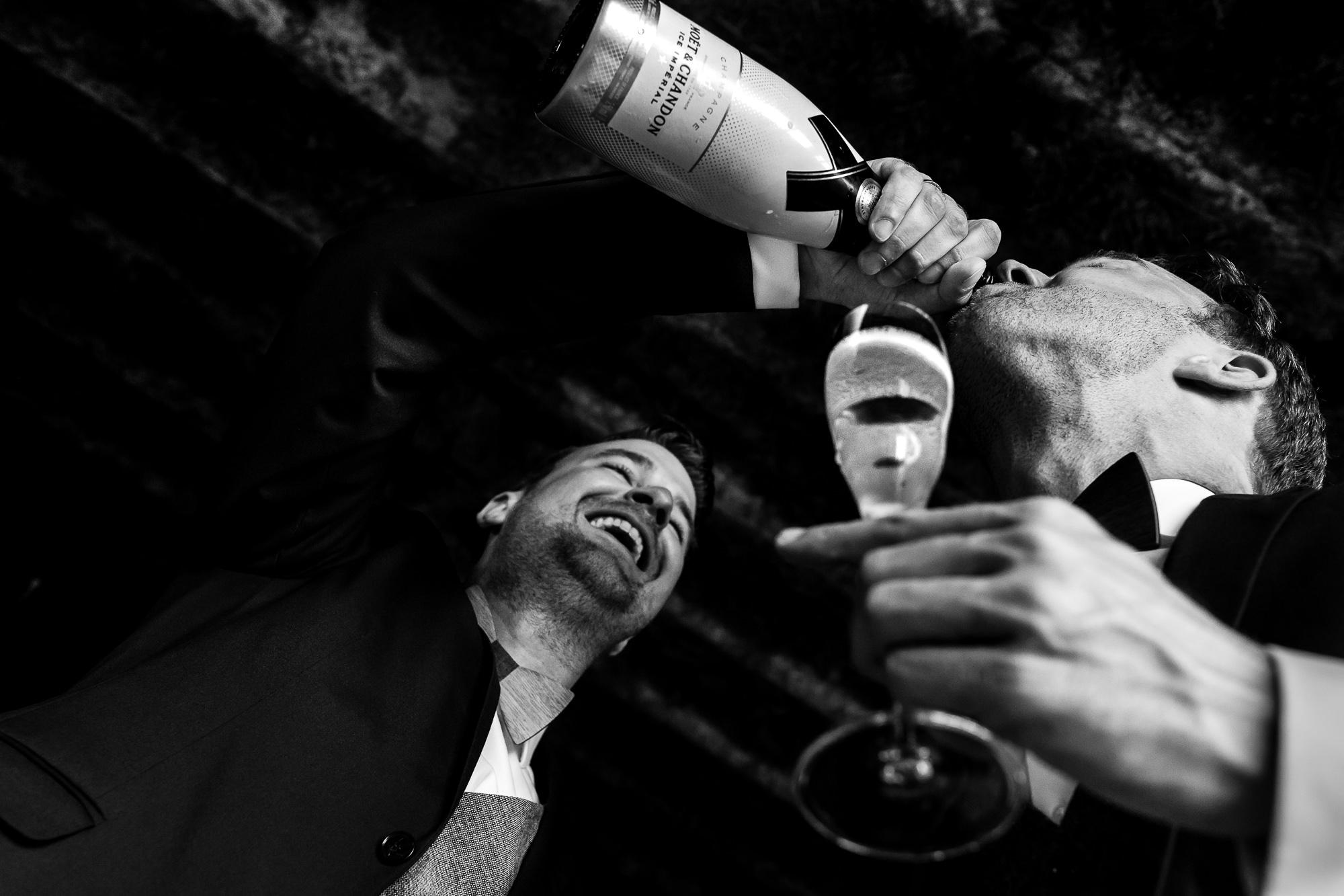 Zwart wit foto van bruidegom die schenkt champagne vanuit de fles bij zijn aanstaande