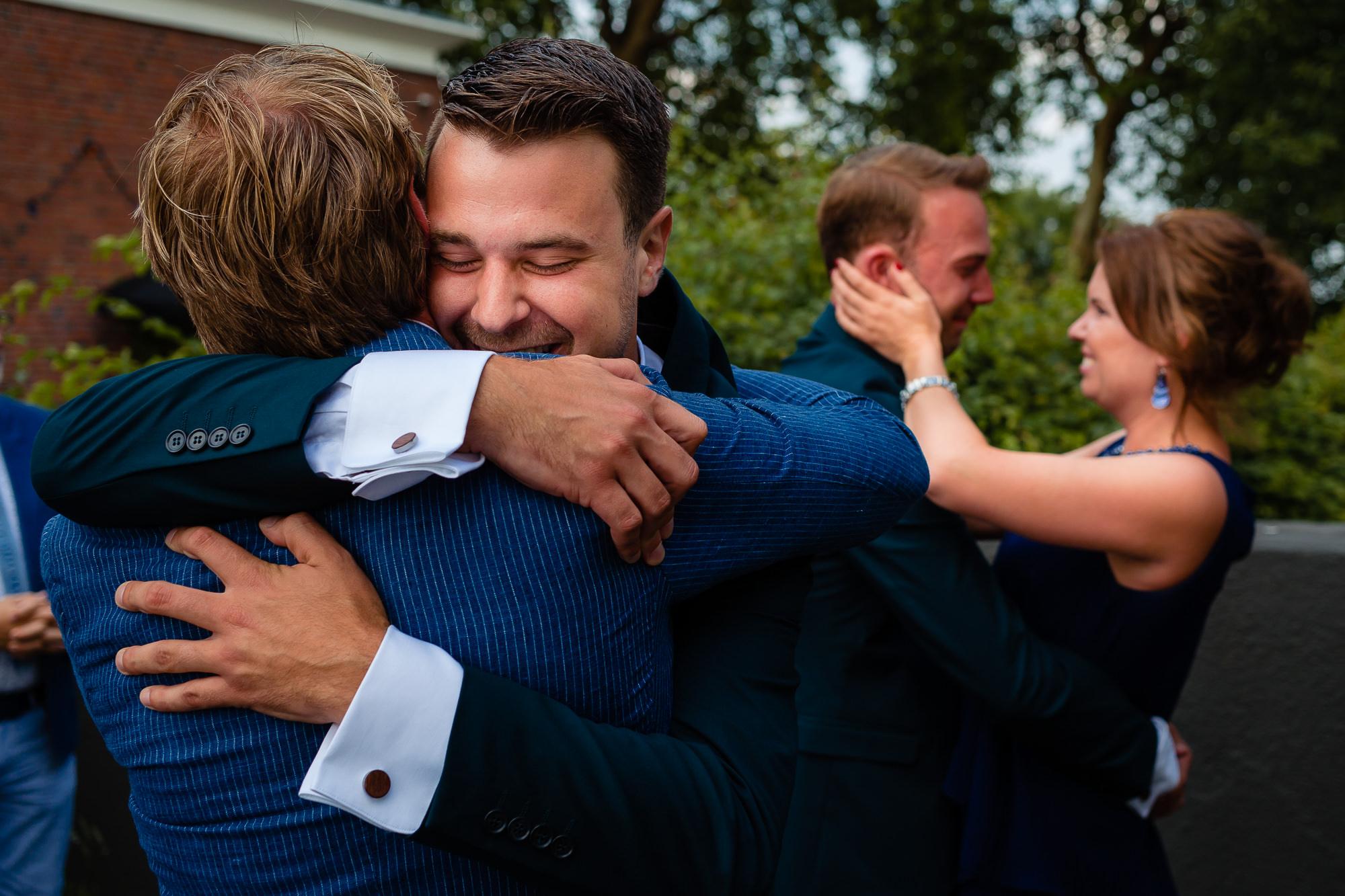 Bruidegoms worden beiden geëmotioneerd geknuffeld