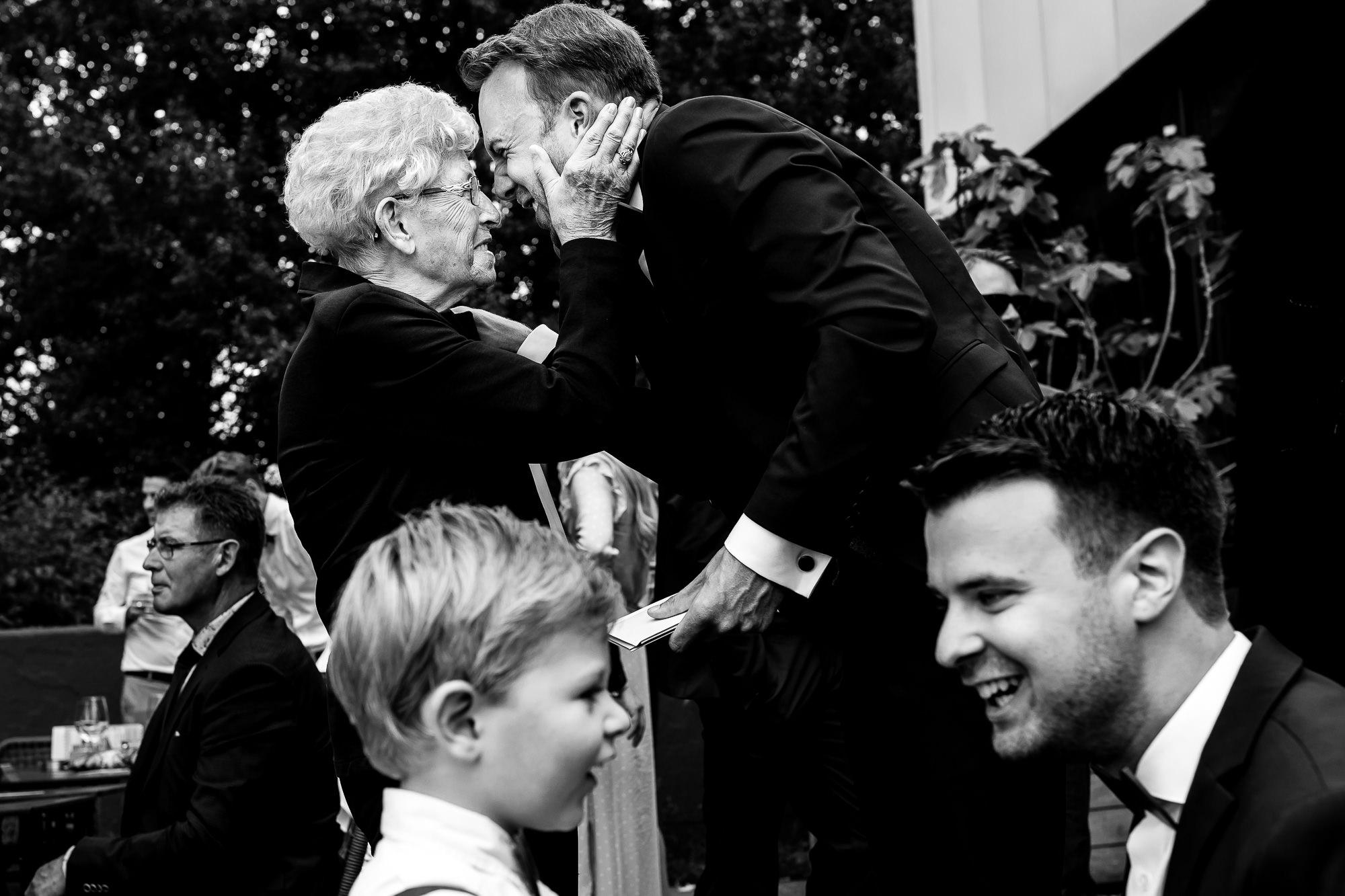 Zwart wit foto van bruidegom die zijn oma knuffelt