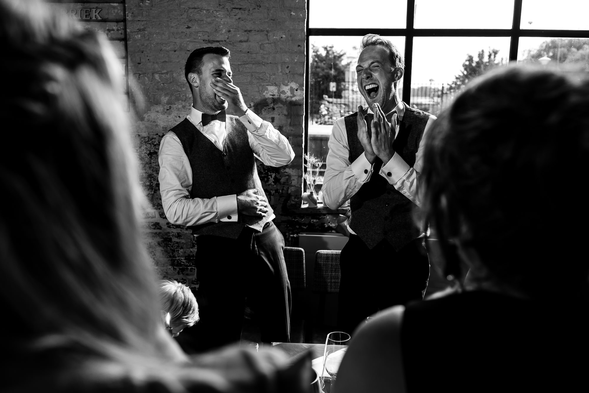 Zwart wit foto van bruidegoms liggen beiden helemaal in een deuk