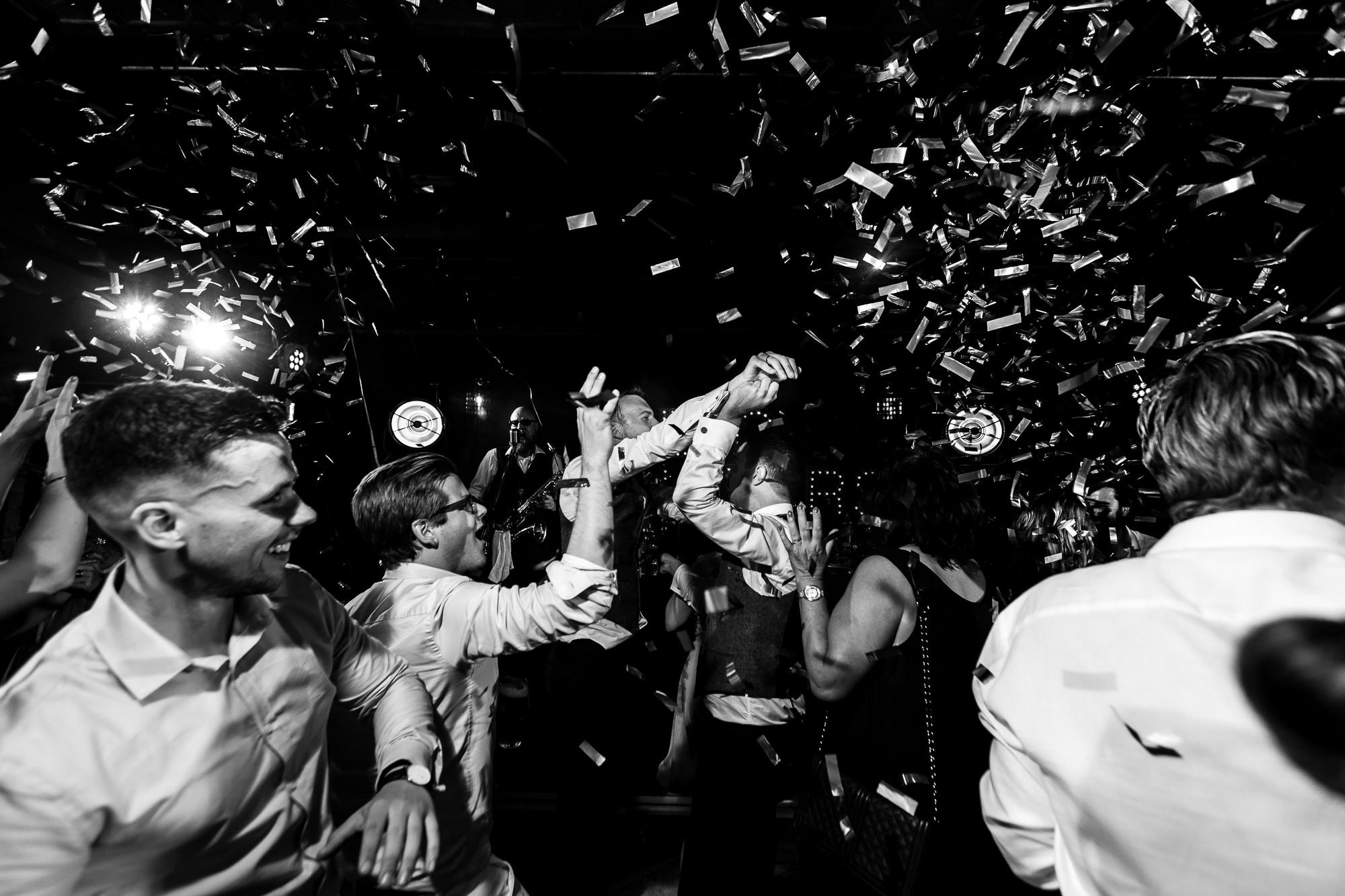 Zwart wit foto van confetti kanon tijdens de trouwfeest