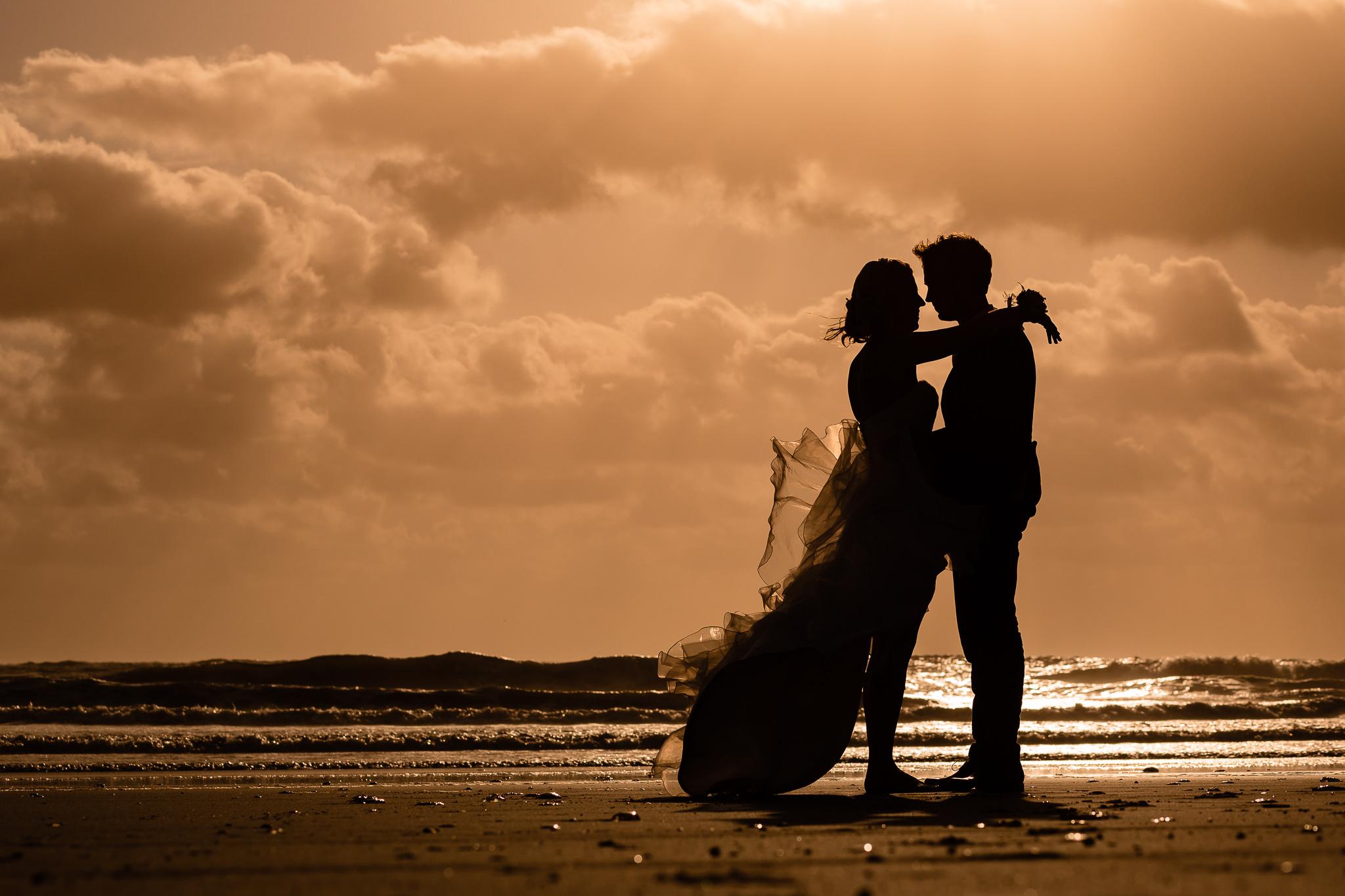 Bruidspaar op het strand op Texel tijdens de zonsondergang