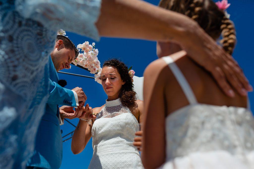 Bruidspaar schuift de ringen bij elkaar om terwijl hun dochter toekijkt