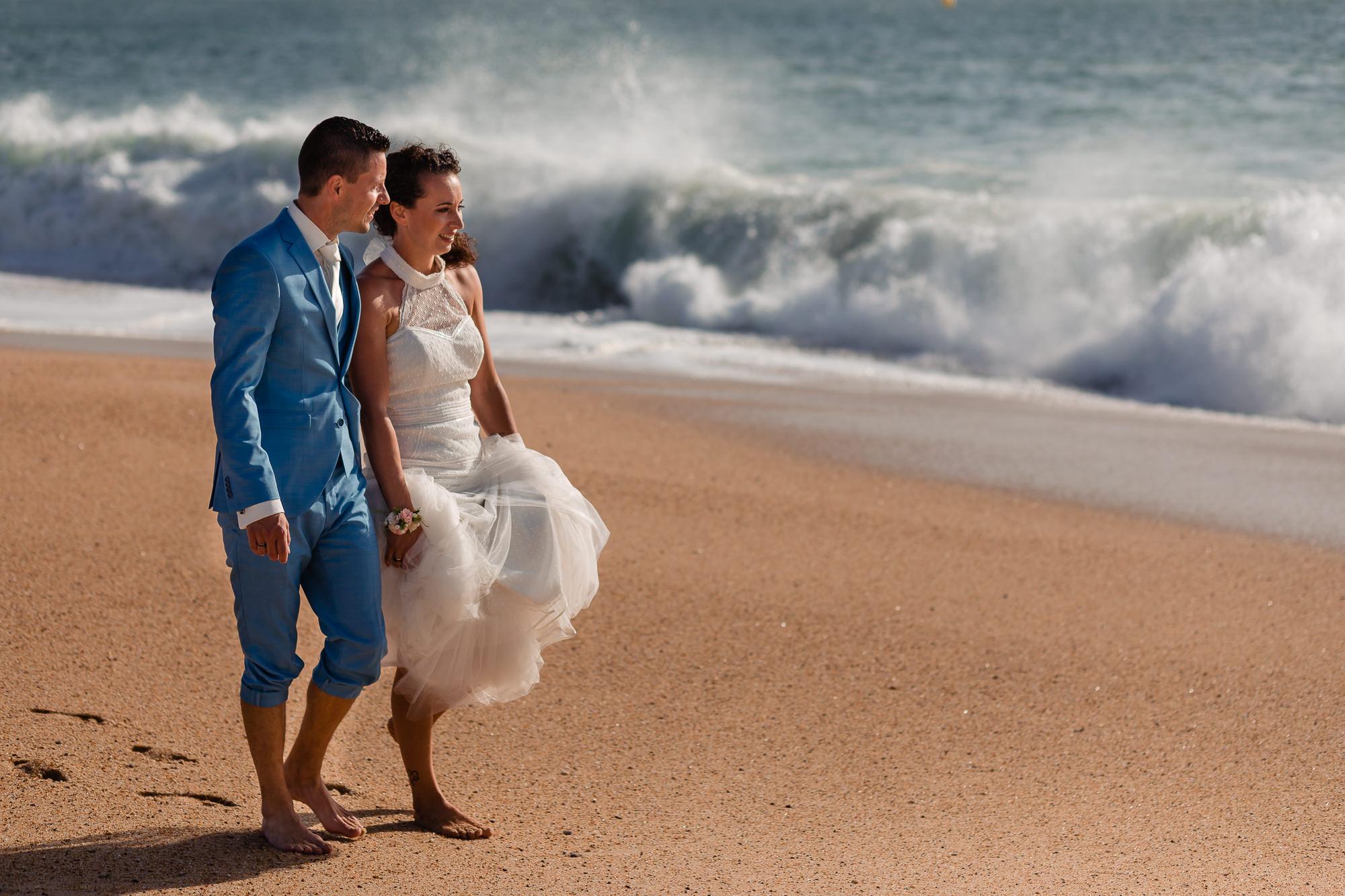 Bruidspaar loopt op het strand met de zee golvend op de achtergrond
