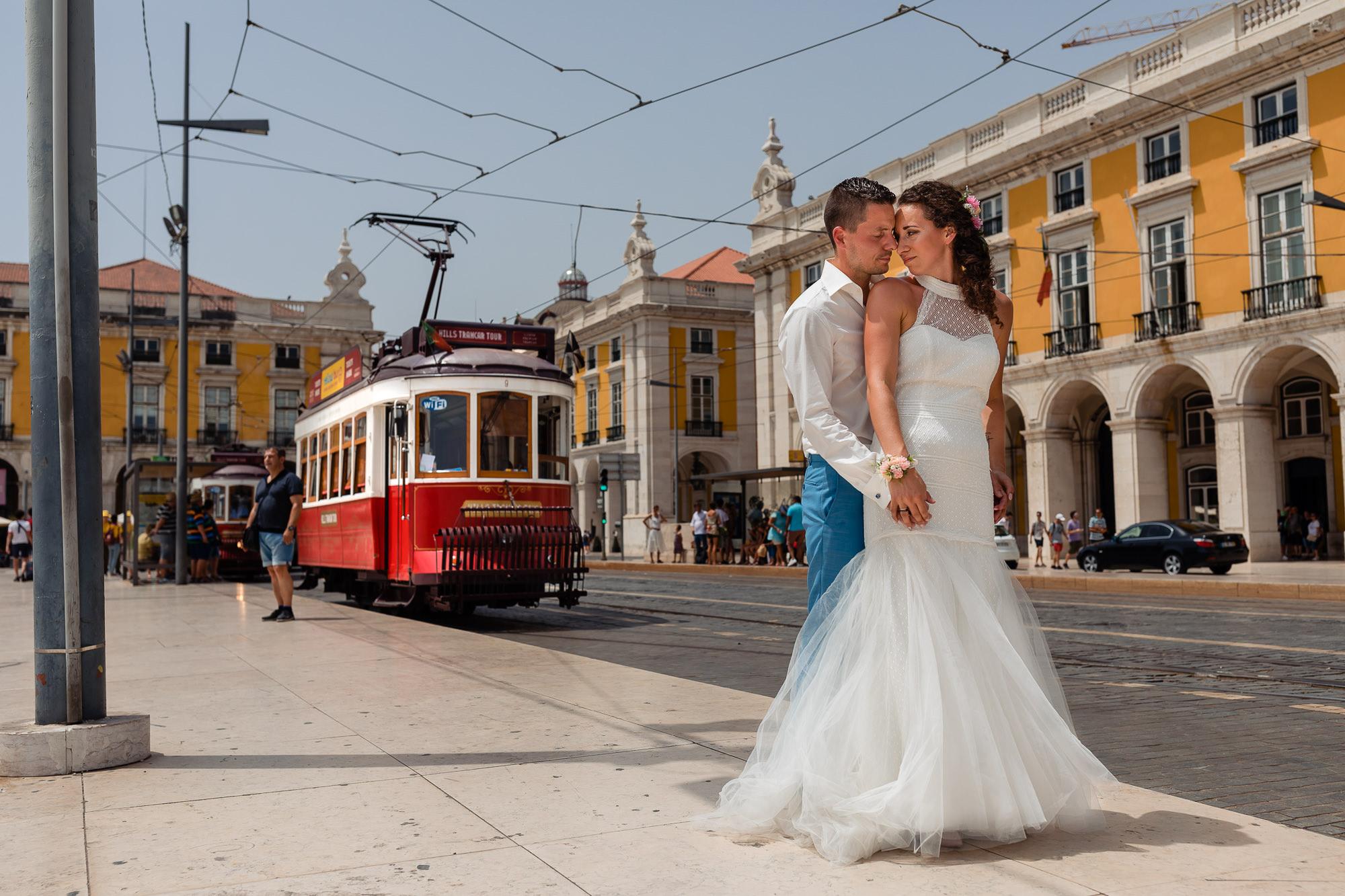 Bruidspaar poseert in Portugal in de stad bij een tram