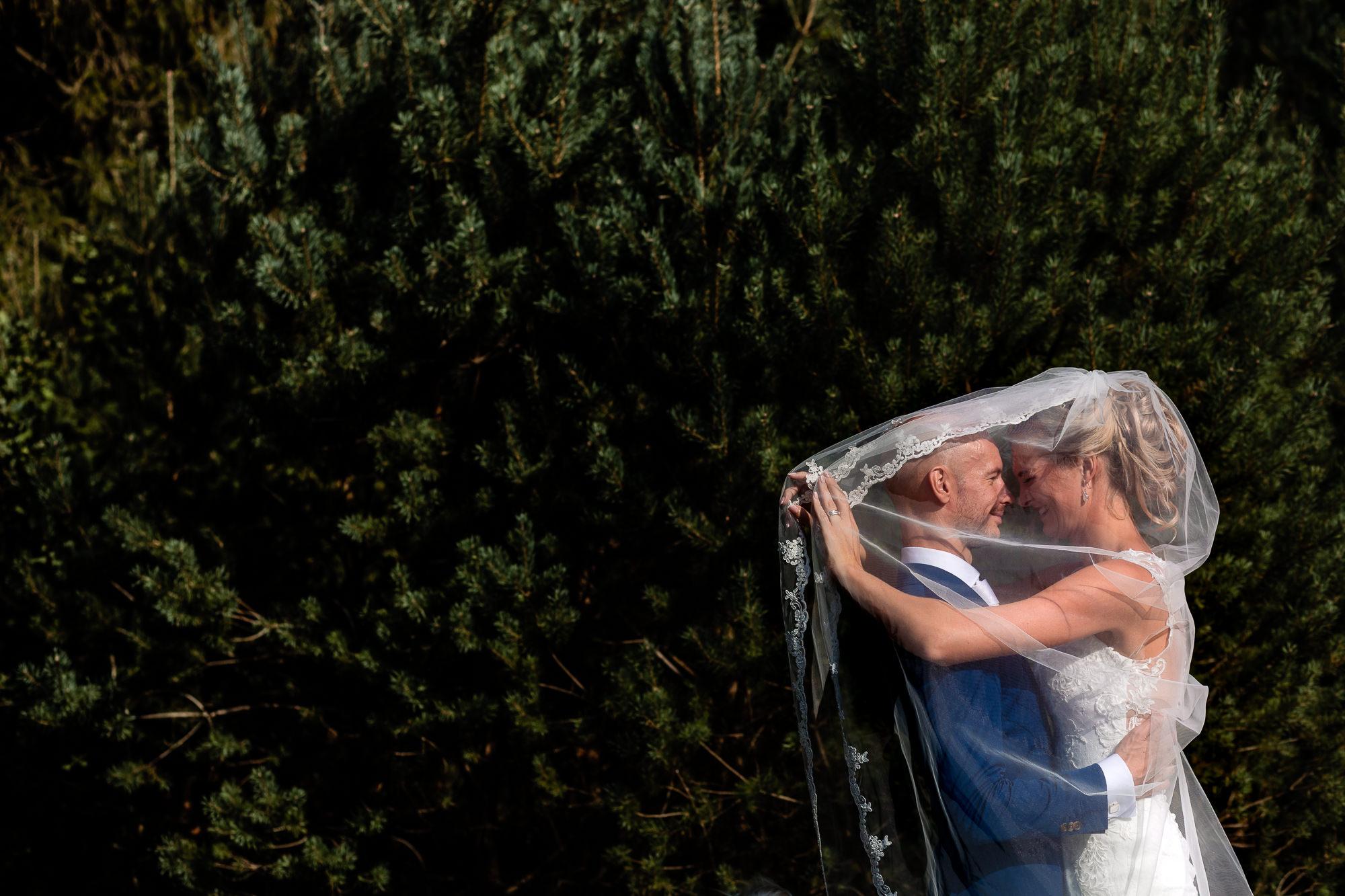 Bruidspaar onder de sluier tijdens de fotoshoot