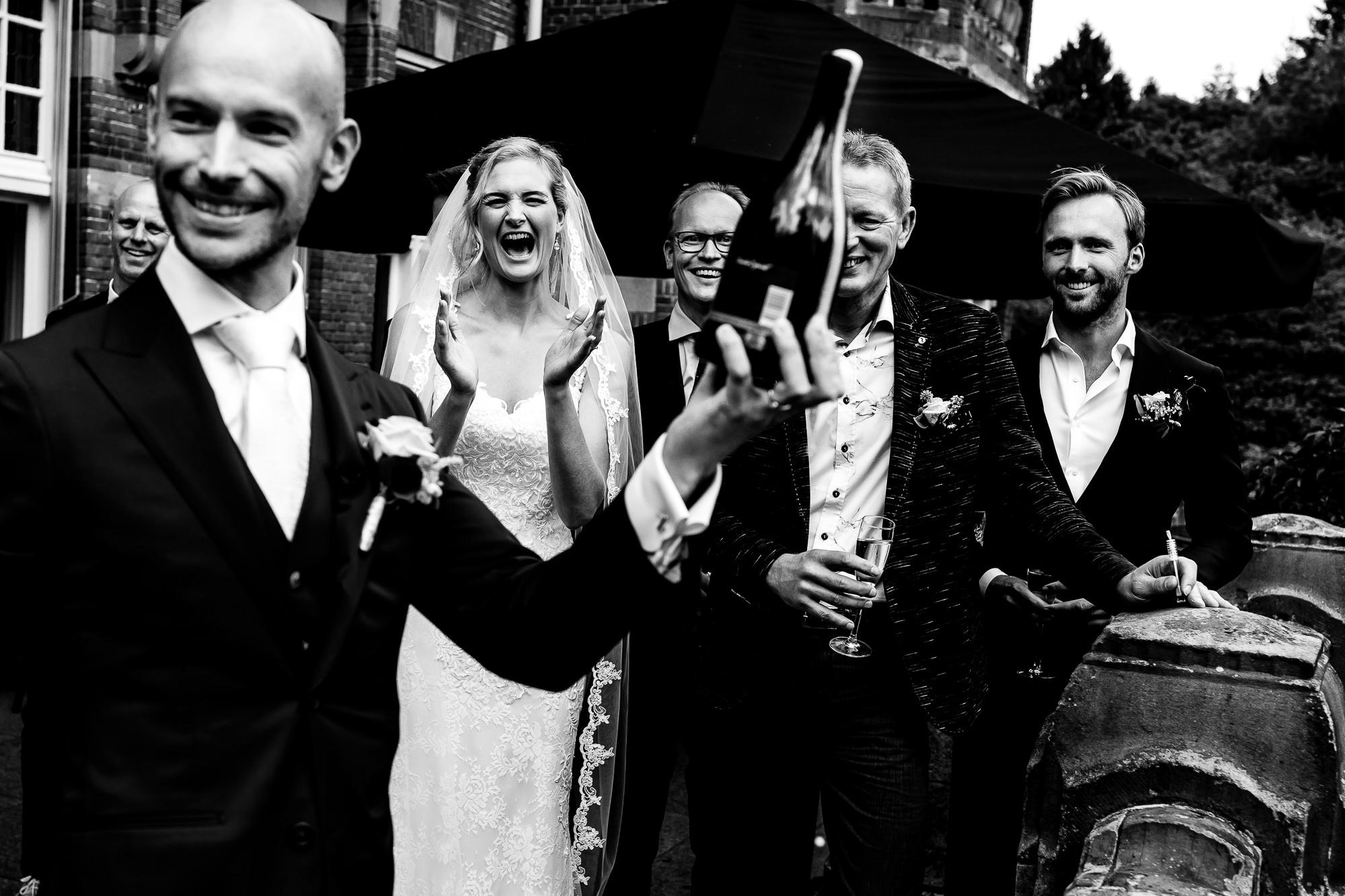 Zwart wit foto van bruidegom die de champagne heeft gesabreerd met de bruid op de achtergrond