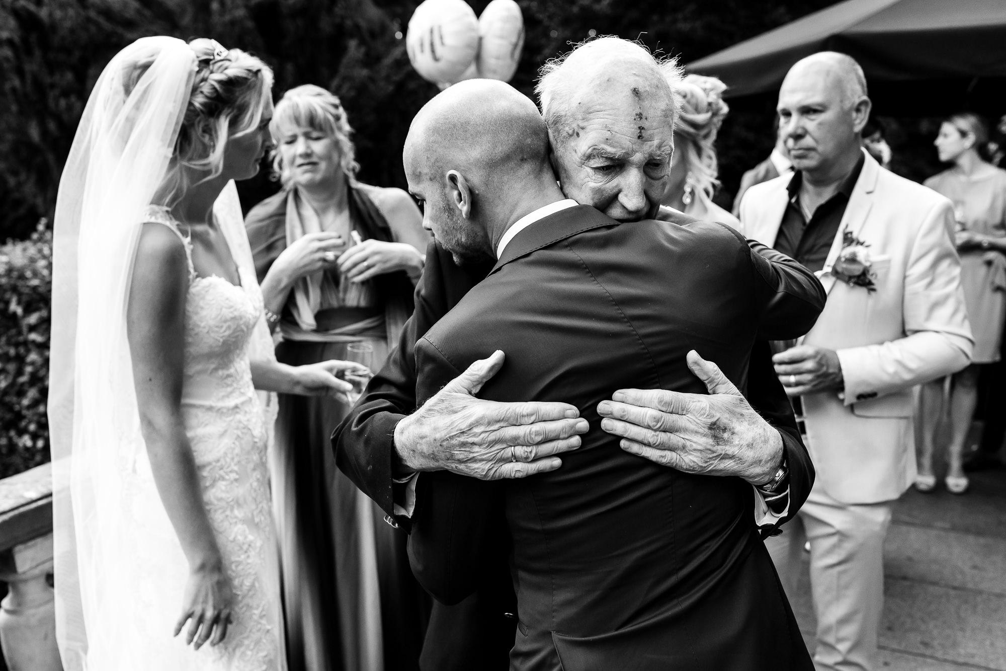 Opa die de bruidegom knuffelt na de ceremonie met de bruid op de achtergond