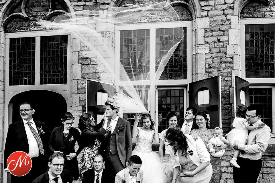 Sluier van de bruid vliegt door de wind omhoog tijdens de groepsfoto