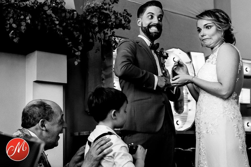 Bruid en bruidegom schuiven elkaar de ringen om en trekken hierbij een gek gezicht