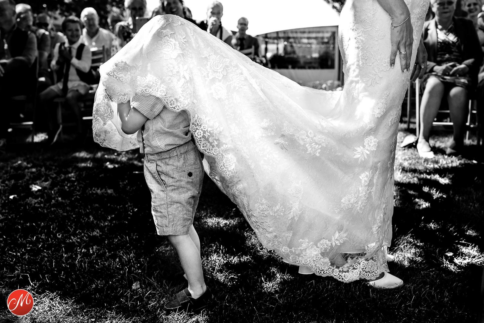 Zwart wit foto van jongen die onder de jurk van de bruid kruipt