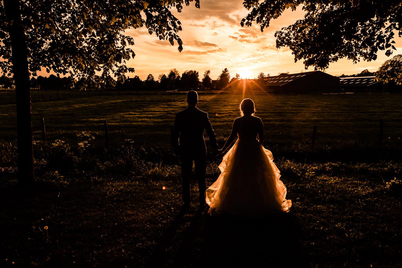 Bruidspaar als silhouet tijdens zonsondergang
