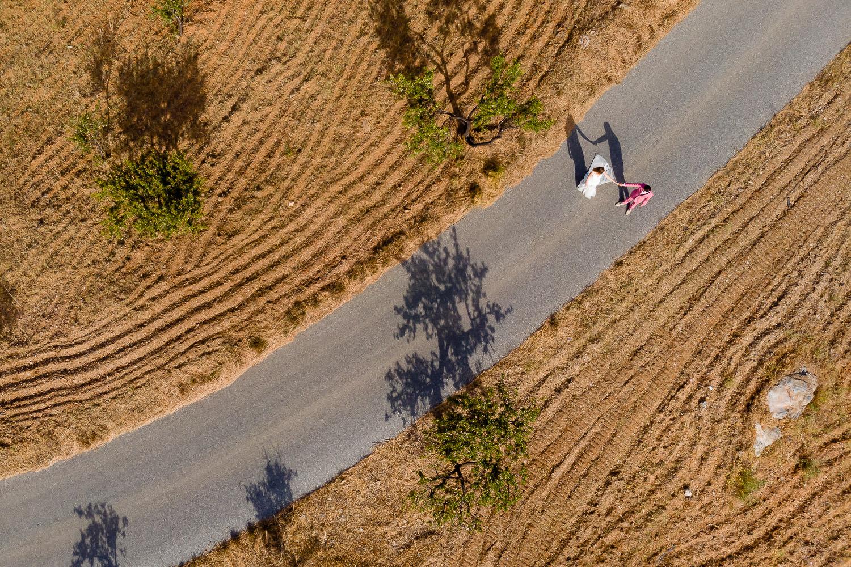 Bruidspaar loopt over een weg van bovenaf gefotografeerd