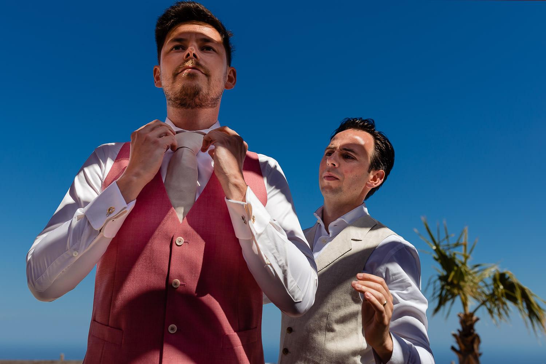 Bruidegom doet zijn stropdas goed en vriend helpt