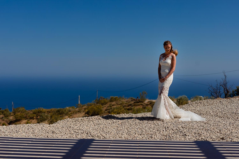 Bruid poseert met de weidse zee op de achtergrond in Spanje