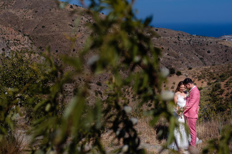 Bruidspaar poseert in een weids heuvelachtig landschap in Spanje