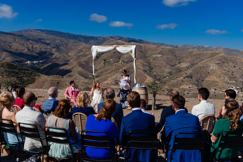 Bruidspaar en hun vrienden en familie luisteren naar de trouwambtenaar