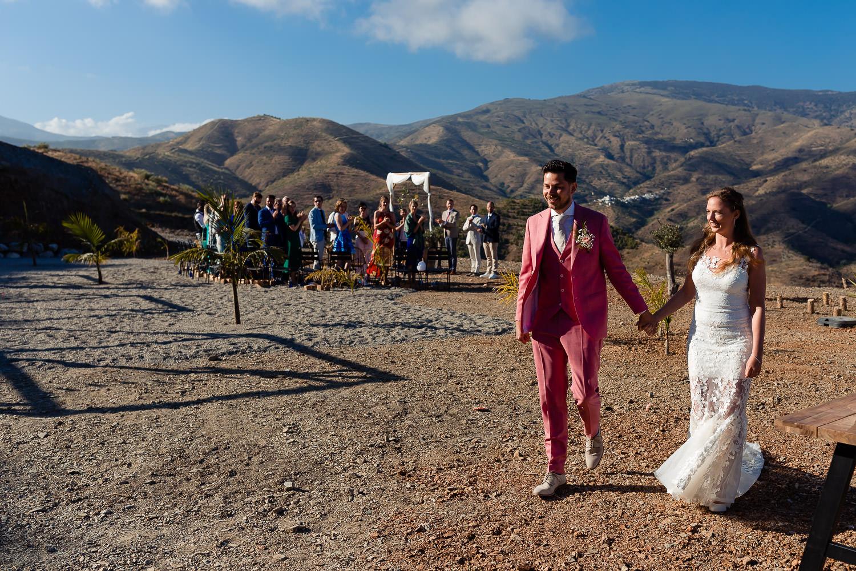 Bruidspaar loopt weg na de ceremonie terwijl de gasten klappen