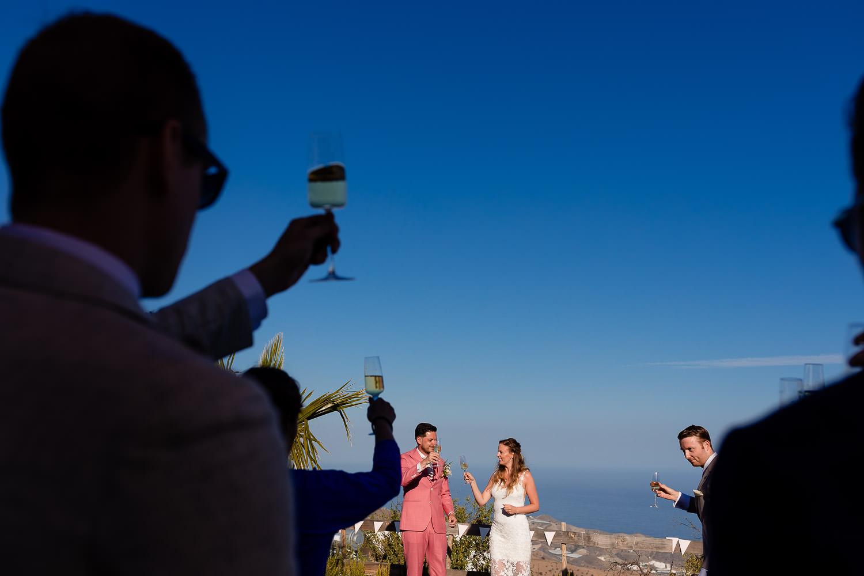Gasten proosten met het bruidspaar op de achtergrond