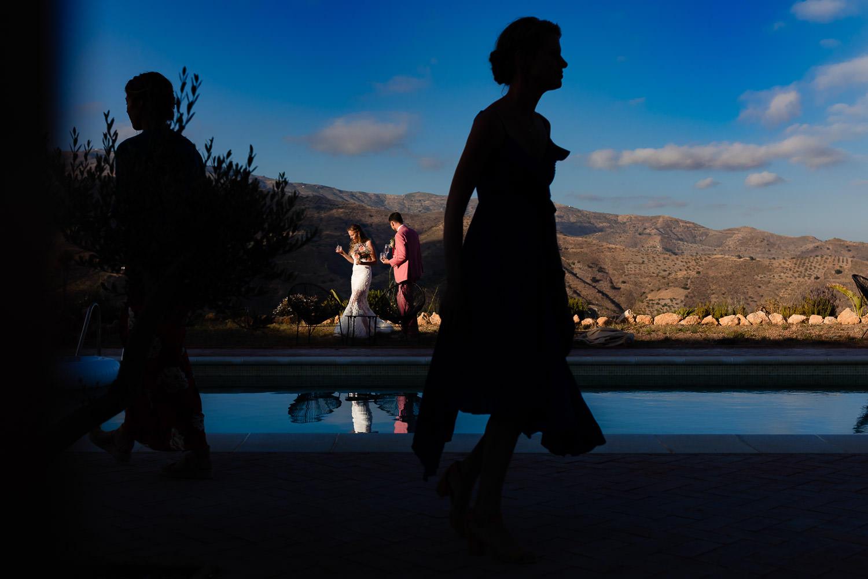 Silhouet van gasten met het bruidspaar op de achtergrond