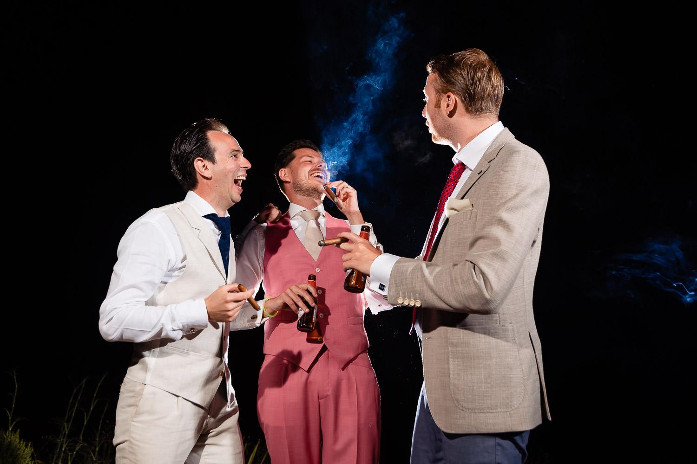 Bruidegom rookt lachend een sigaar met zijn vrienden met een donkere achtergrond