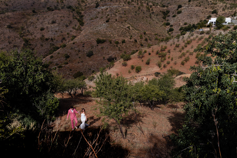 Bruidspaar van bovenaf gefotografeerd in een heuvelachtig landschap in Spanje