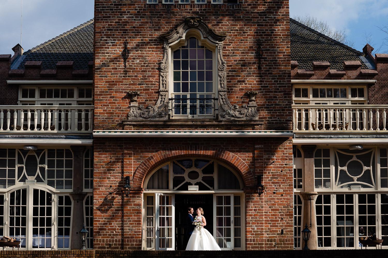 Bruidspaar poseert voor een historisch gebouw