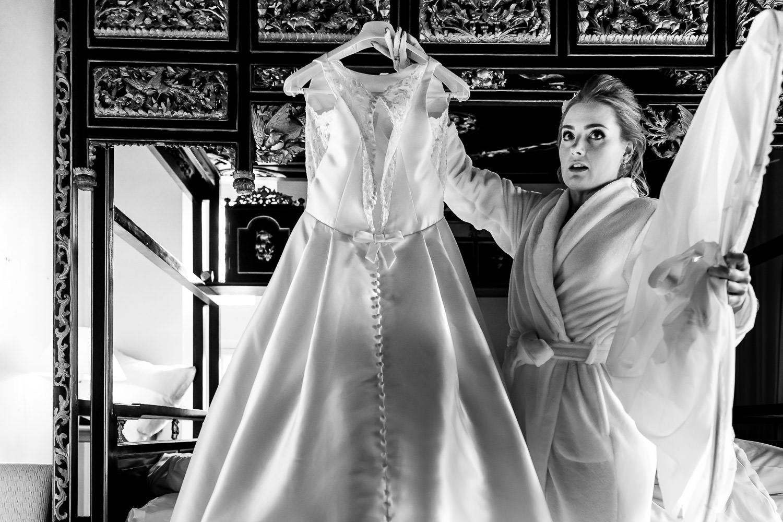 Zwart wit foto van een bruid in badjas houdt haar trouwjurk vast om hem aan te doen