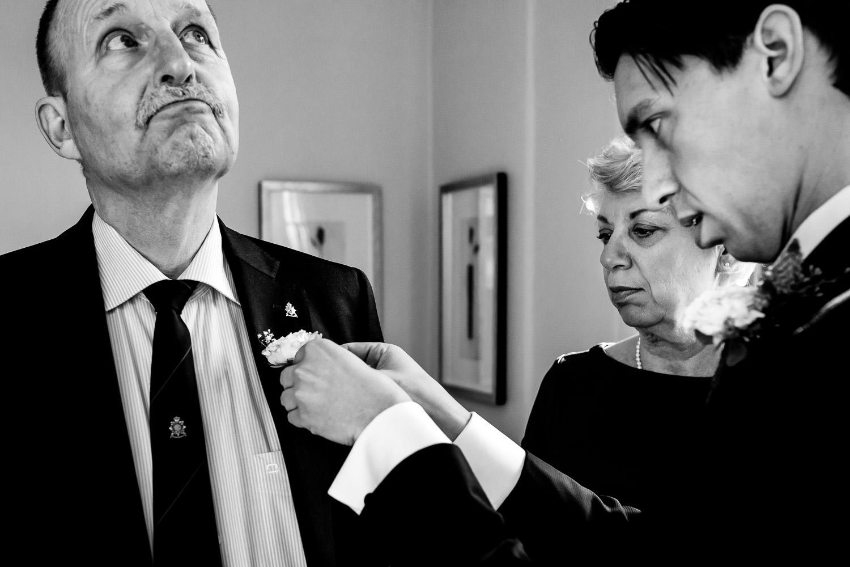Zwart wit foto van bruidegom die de corsage opdoet bij zijn vader met behulp van zijn moeder