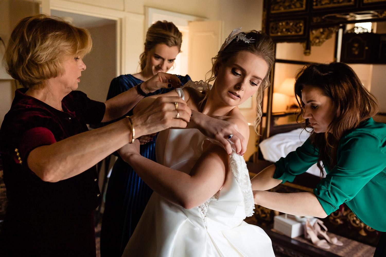 Drie vrouwen helpen de bruid bij het aantrekken van haar jurk