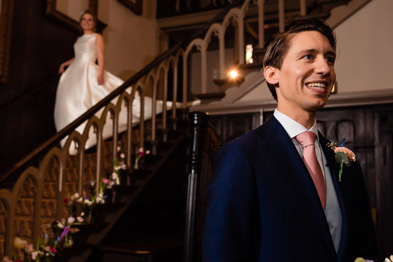 Een verliefde bruidegom staat met zijn rug naar de trap en wacht op bruid die de trap afloopt