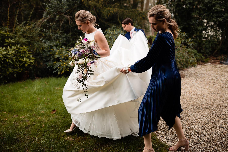 Bruidegom en vriendin helpen bruid met het optillen van de jurk terwijl ze loopt