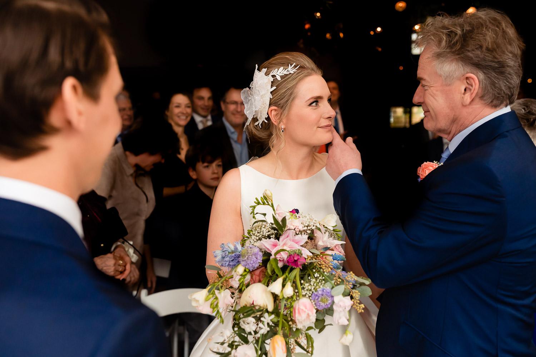Vader strijkt met zijn hand over de wang van zijn dochter terwijl de bruidegom toekijkt