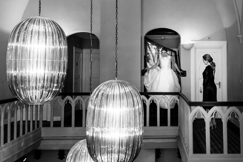 Zwart wit foto van de bruid die de trap afloopt