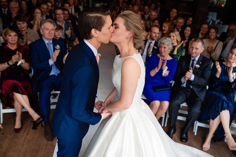 Bruidspaar kust elkaar terwijl de familie en vrienden klappend toekijken