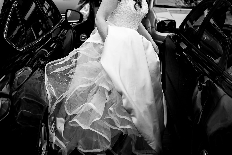 Zwart wit foto van de jurk van de bruid terwijl ze tussen de auto's doorloopt